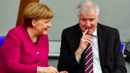 Bundeskanzlerin Angela Merkel (CDU) unterhält sich im Bundestag bei ihrer ersten Regierungserklärung nach ihrer Wiederwahl zur Regierungschefin mit Horst Seehofer (CSU).