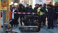 Ein Sprengstoffroboter steht am vor einer Bankfiliale in Berlin-Steglitz, in der am Freitag eine verdächtige Versandtasche entdeckt worden ist.