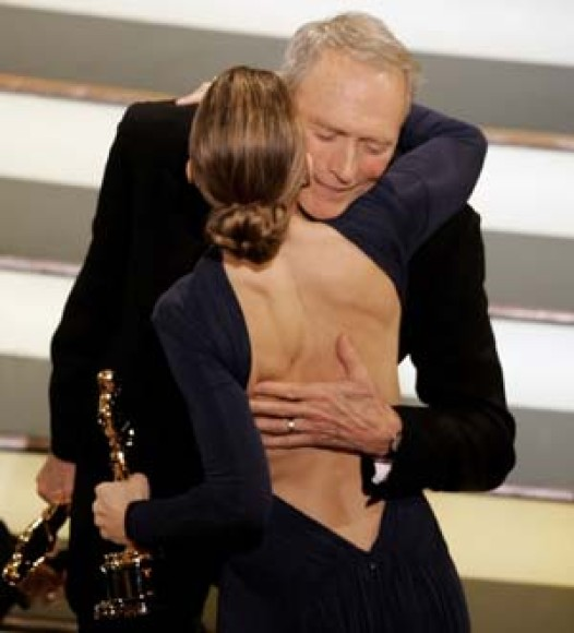 Clint Eastwood embraces Hilary Swank after winning the Oscar for best picture at the 77th Academy Awards