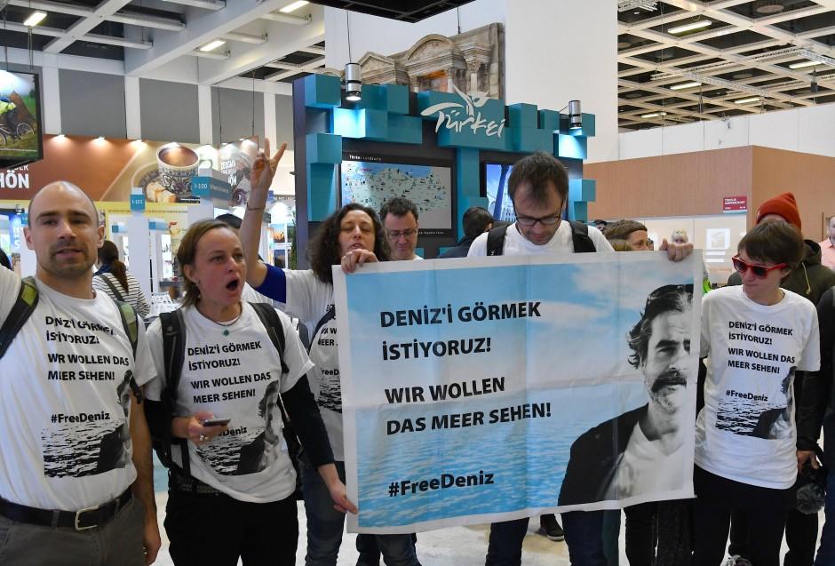 Auf der diesjährigen ITB wurde es immer wieder politisch: Demonstranten halten in der Türkei-Halle ein Transparent mit dem Foto des in der Türkei inhaftierten Journalisten Deniz Yücel in die Höhe.