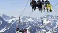 Skifahrer in einem Sessellift der Nebelhornbahn.