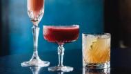 Ein Cocktail auf den Sieg: Beim Bellini (links) trifft Champagner auf Pfirsichmark. Wer es eine Spur süßer mag, der sollte zum Himbeer-Daiquiri (Mitte) greifen. Der Fex (rechts) ist der Geheimtipp dieses Sommers: Gin mit Gurke und Minze