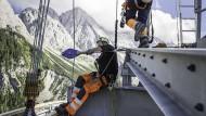 Drahtseilakt: Arbeiter montieren einen Rollensattel an der Stütze. Es gibt unterwegs nur eine Stütze, die ist 127 Meter hoch. Die Seilbahn wird von der Firma Garaventa hergestellt.